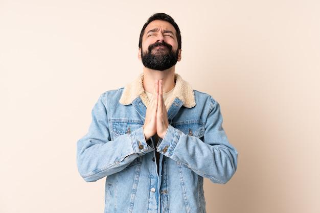Hombre caucásico con barba sobre la pared mantiene la palma de la mano.