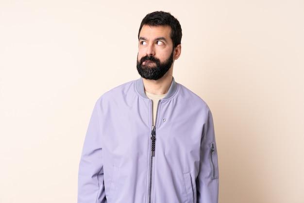 Hombre caucásico con barba vistiendo una chaqueta sobre espacio aislado teniendo dudas mientras mira hacia arriba