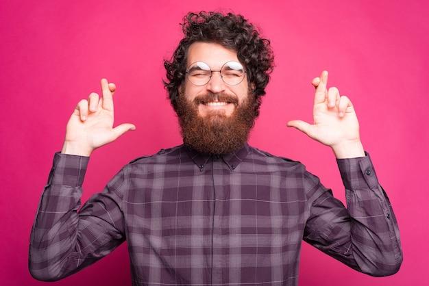 Hombre caucásico barbudo alegre cruzando los dedos y soñando con un gran sueño