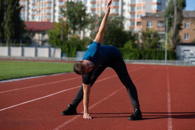 Hombre caucásico barbudo se calienta antes de entrenar en la pista de atletismo. espacio vacio