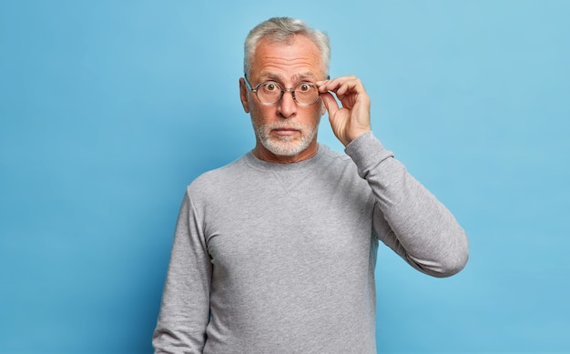 Hombre caucásico barbudo senior sorprendido que mira a través de anteojos expresa conmoción maravillas descuentos estacionales y precios escucha noticias increíbles usa jersey gris casual aislado sobre pared azul
