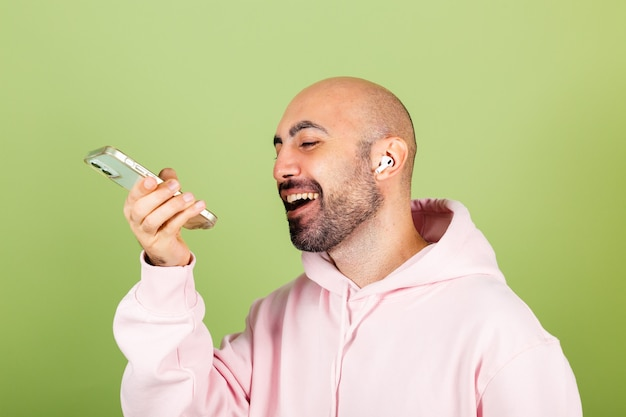 Hombre caucásico calvo joven en sudadera con capucha rosa aislado, sostenga el mensaje de audio de grabación positiva feliz del teléfono
