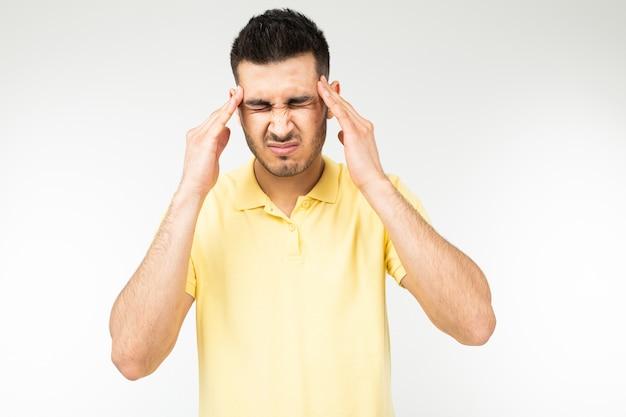 Hombre caucásico con una camiseta amarilla tiene dolor de cabeza sobre un fondo blanco de estudio.
