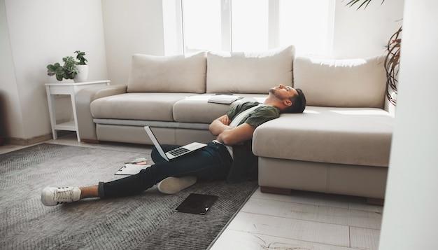 Hombre caucásico cansado dormirse en el suelo con una computadora y tableta con las manos cruzadas