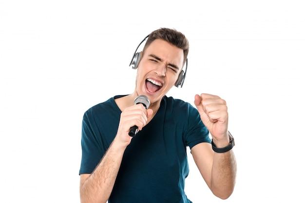 El hombre caucásico está cantando la canción en el micrófono.