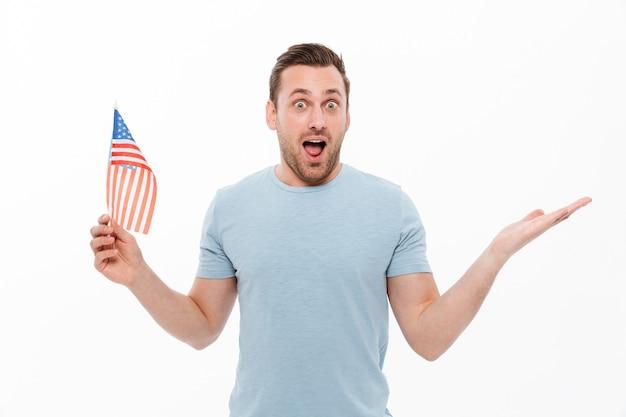 Hombre caucásico con cerdas sosteniendo pequeña bandera americana y levantando la mano en sorpresa