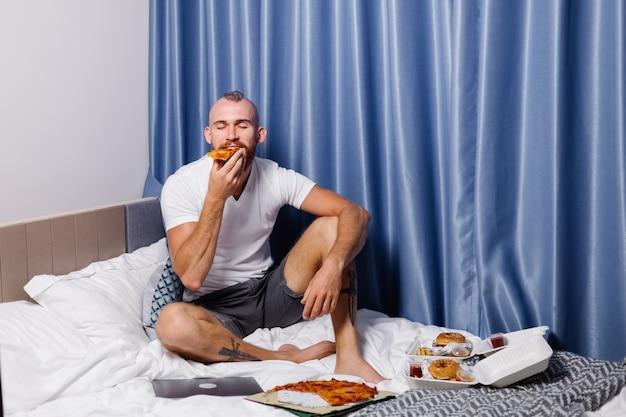 Hombre caucásico con comida rápida en casa en el dormitorio en la cama