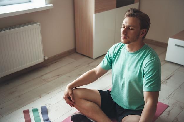 Hombre caucásico concentrado con cerdas y cabello largo meditando sobre una alfombra de yoga en el suelo en casa