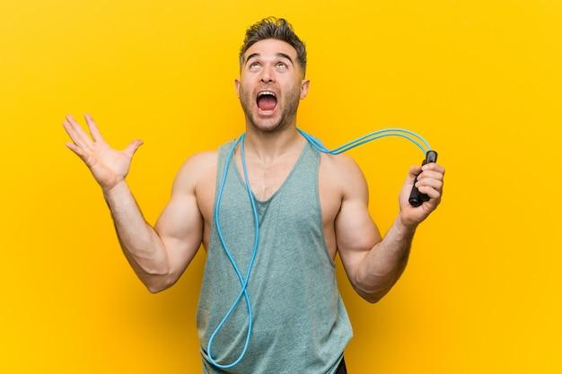 Hombre caucásico con una cuerda de saltar celebrando una victoria o éxito