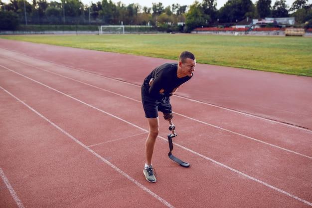 Hombre caucásico deportivo con pierna artificial de pie en pista de atletismo y dolor de estómago.