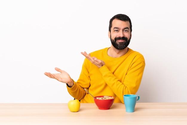 Hombre caucásico desayunando en una mesa extendiendo las manos hacia un lado para invitar a venir.