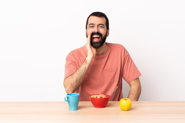 Hombre caucásico desayunando en una mesa gritando con la boca abierta.