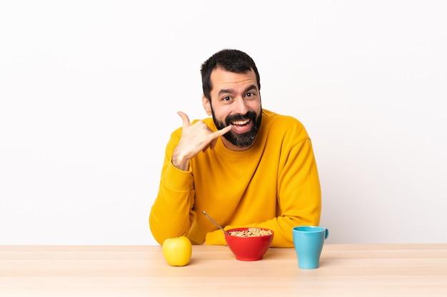 Hombre caucásico desayunando en una mesa haciendo gesto de teléfono. llámame señal de vuelta.