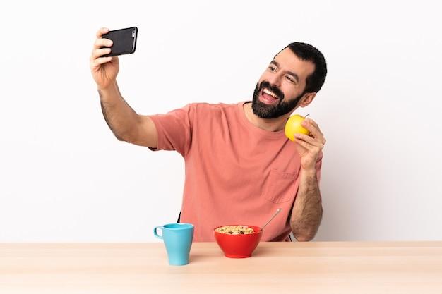 Hombre caucásico desayunando en una mesa haciendo un selfie.