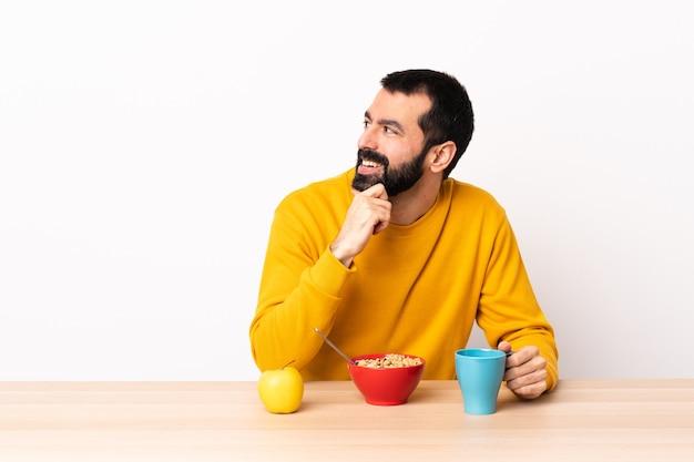 Hombre caucásico desayunando en una mesa mirando hacia un lado y sonriendo.