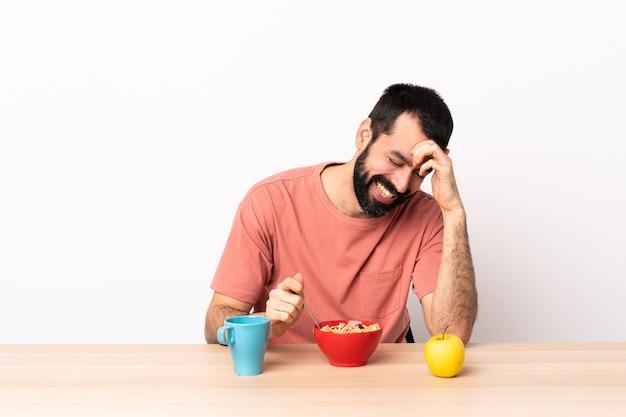 Hombre caucásico desayunando en una mesa riendo.