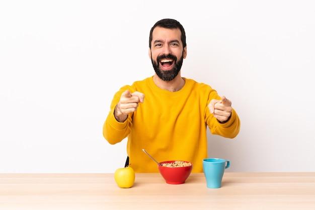 Hombre caucásico desayunando en una mesa sorprendido y apuntando al frente.