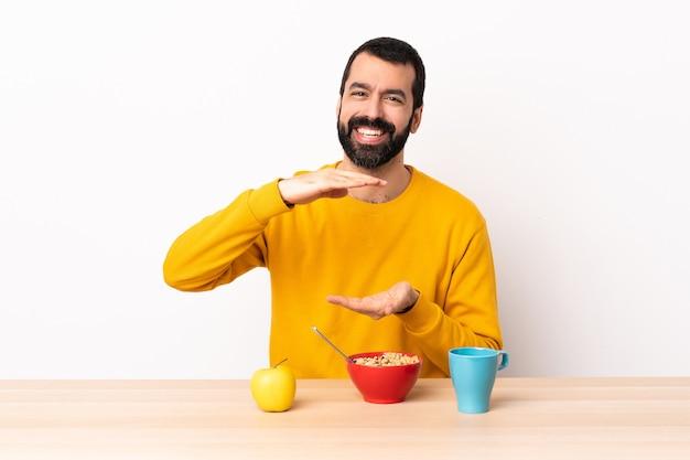 Hombre caucásico desayunando en una mesa sosteniendo copyspace imaginario en la palma para insertar un anuncio.