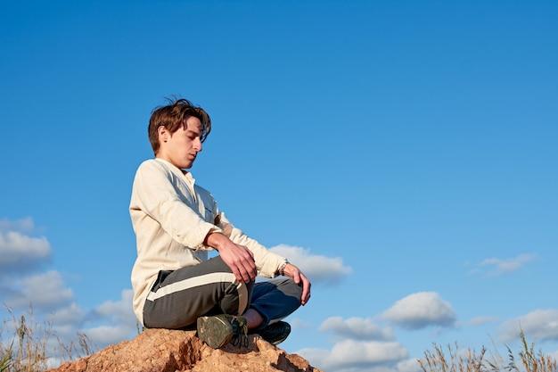 Un hombre caucásico de españa con una camisa beige meditando en una posición sentada sobre fondo de cielo nublado