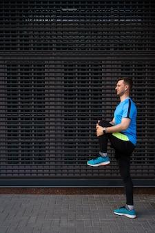 Hombre caucásico estiramiento mientras entrenamiento de la ciudad