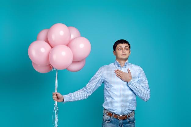 Hombre caucásico feliz en camisa con globos rosados aislados en azul