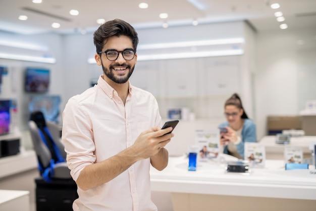 Hombre caucásico feliz con nuevo teléfono inteligente en manos. concepto de nuevas tecnologías.