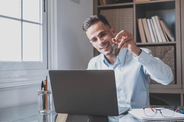 Un hombre caucásico feliz sonriendo y hablando con clientes en línea en videoconferencia mostrándoles las llaves de su casa. trabajador ocupado usando laptop o computadora trabajando.