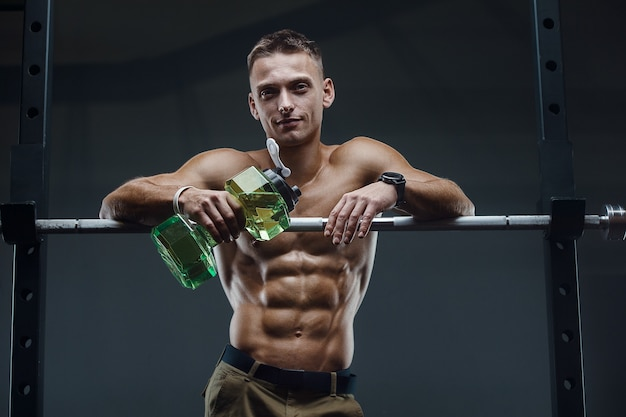 Hombre caucásico fitness agua potable después de hacer ejercicio en el gimnasio.