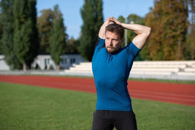 Hombre caucásico fuerte calienta antes de entrenar en la pista de atletismo. espacio vacio