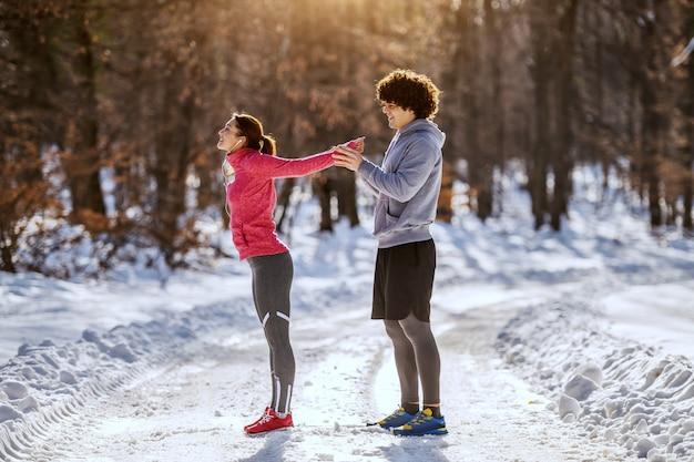 Hombre caucásico guapo ayudando a su amiga a estirar los brazos mientras está de pie en el sendero. invierno concepto de gimnasio al aire libre.