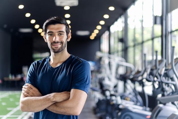 Hombre caucásico guapo con barba en ropa deportiva de color azul de pie y cruzando los brazos en el gimnasio o club de fitness.
