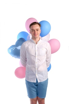 Hombre caucásico guapo en camisa blanca sonriendo y sosteniendo en forma de saludos globos rosados y azules, aislados