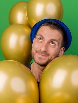Hombre caucásico guapo satisfecho con sombrero de fiesta azul se encuentra con globos de helio mirando hacia arriba aislado sobre fondo verde con espacio de copia