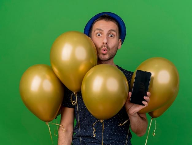Hombre caucásico guapo sorprendido con sombrero de fiesta azul se encuentra con globos de helio y sostiene el teléfono aislado sobre fondo verde con espacio de copia
