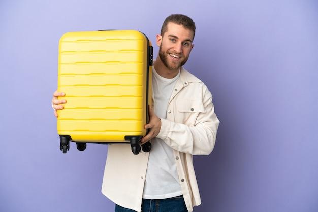 Hombre caucásico hermoso joven aislado en la pared púrpura en vacaciones con maleta de viaje y sorprendido
