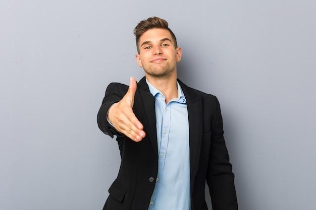 Hombre caucásico hermoso joven que estira la mano en gesto de saludo.