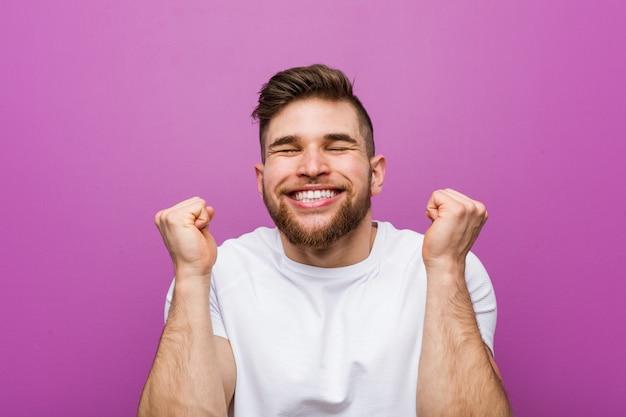 Hombre caucásico hermoso joven que levanta el puño, sintiéndose feliz y acertado. concepto de victoria