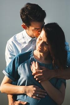Hombre caucásico joven abrazando a esposa embarazada