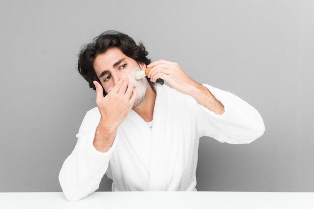Hombre caucásico joven afeitarse la barba aislado en una pared gris
