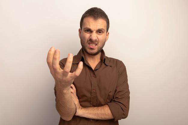 Hombre caucásico joven agresivo poniendo la mano en el brazo estirando la mano hacia la cámara mirando a cámara aislada sobre fondo blanco con espacio de copia