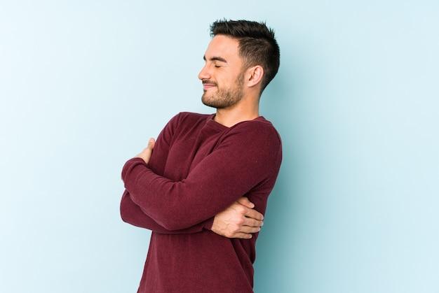 Hombre caucásico joven aislado en abrazos azules, sonriendo despreocupado y feliz.