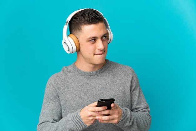 Hombre caucásico joven aislado escuchando música con un móvil y pensando