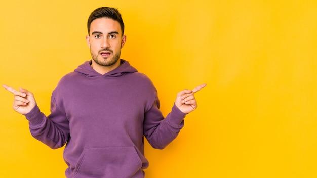Hombre caucásico joven aislado en la pared amarilla apuntando a diferentes espacios de copia, eligiendo uno de ellos, mostrando con el dedo.