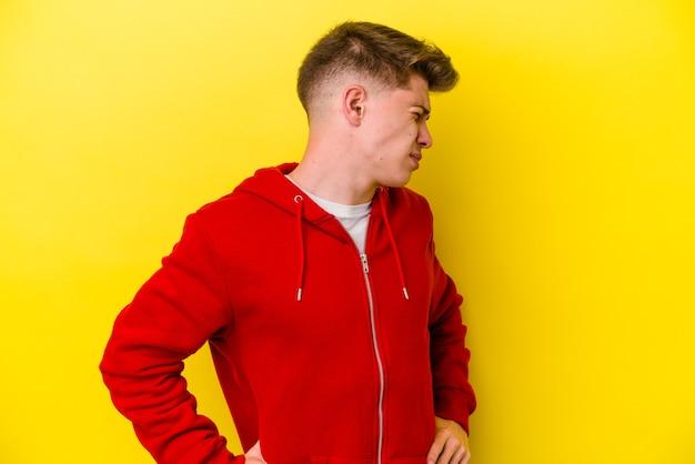 Hombre caucásico joven aislado en la pared amarilla que sufre un dolor de espalda