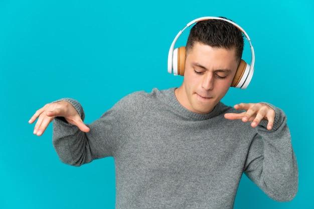 Hombre caucásico joven aislado en la pared azul escuchando música y bailando