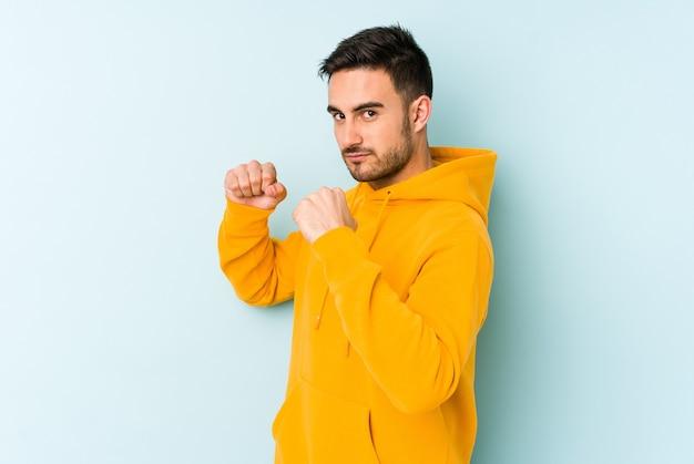 Hombre caucásico joven aislado en la pared azul lanzando un puñetazo, ira, luchando debido a una discusión, boxeo.