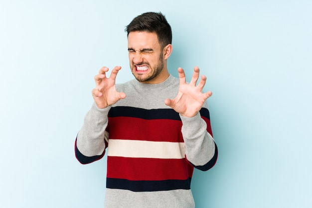 Hombre caucásico joven aislado en la pared azul mostrando garras imitando a un gato, gesto agresivo.