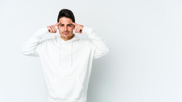 Hombre caucásico joven aislado en la pared blanca se centró en una tarea, manteniendo los dedos índice apuntando la cabeza.