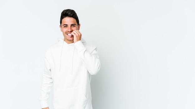 Hombre caucásico joven aislado en la pared blanca mordiéndose las uñas, nervioso y muy ansioso.