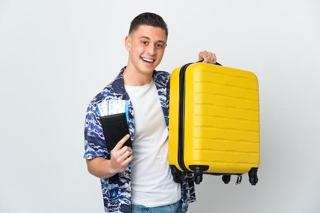 Hombre caucásico joven aislado en la pared blanca en vacaciones con maleta y pasaporte